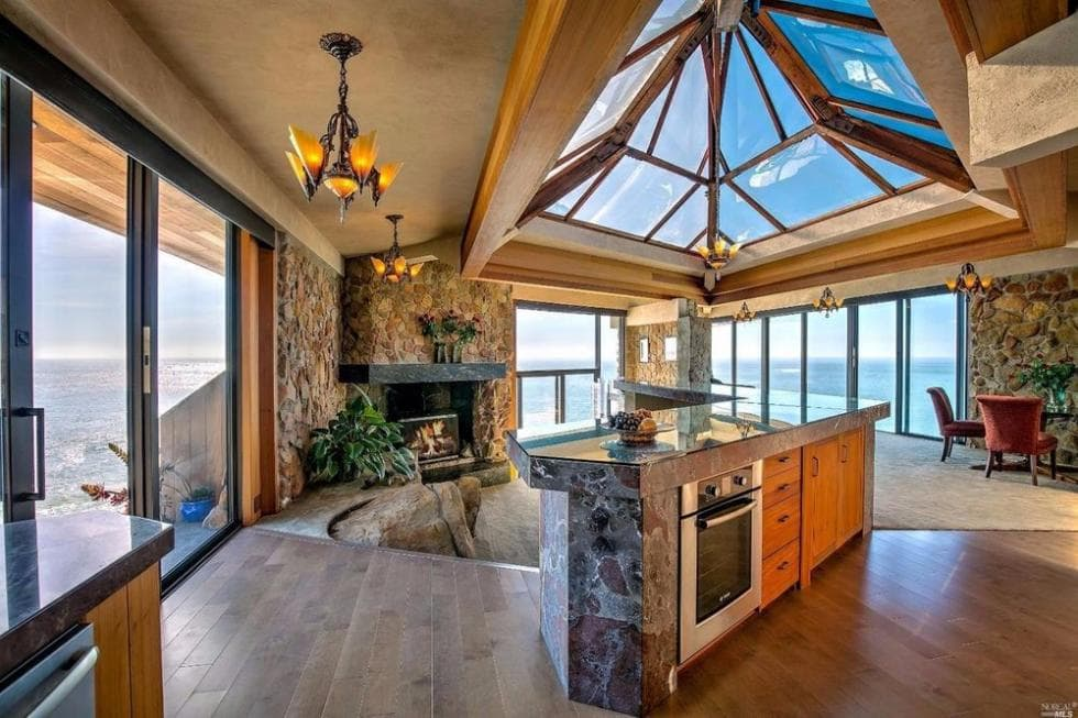 This is the kitchen with a large kitchen island underneath the arched skylight glass ceiling that brings in an abundance of natural lighting. Image courtesy of Toptenrealestatedeals.com.