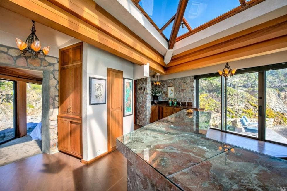 This other view of the kitchen shows the marble countertop of the kitchen island. This pairs well with the wooden accents of the room as well as the doors. Image courtesy of Toptenrealestatedeals.com.