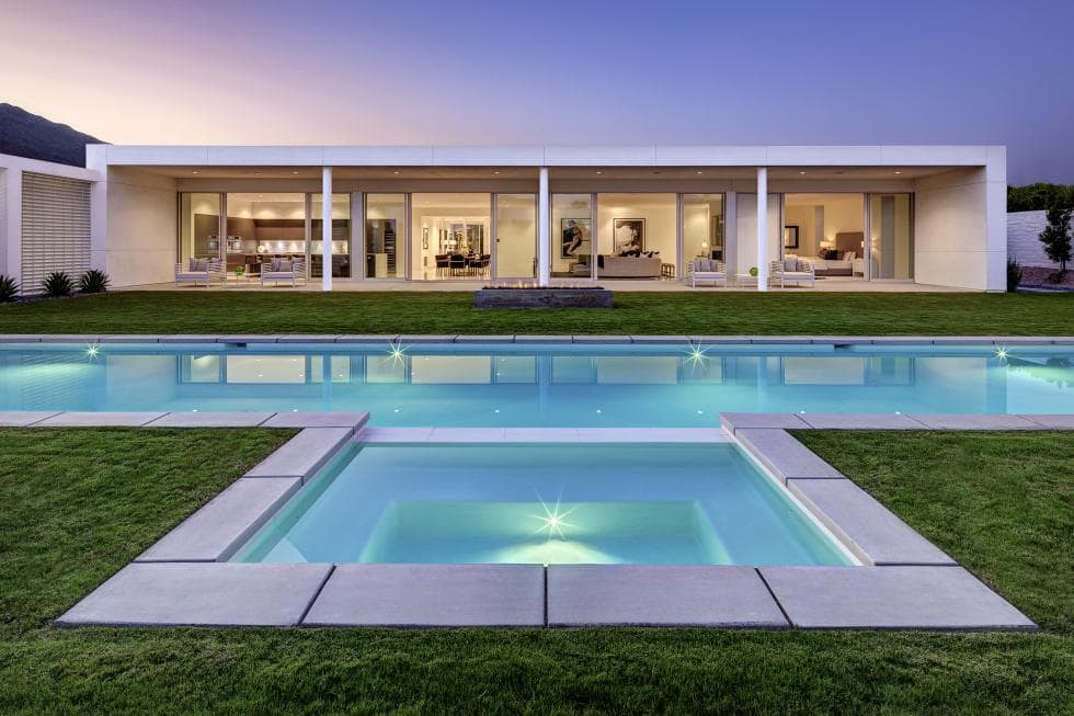 This is a look at the back of the house with a wide glas wall and a large swimming pool surrounded by well-manicured grass. Image courtesy of Toptenrealestatedeals.com.