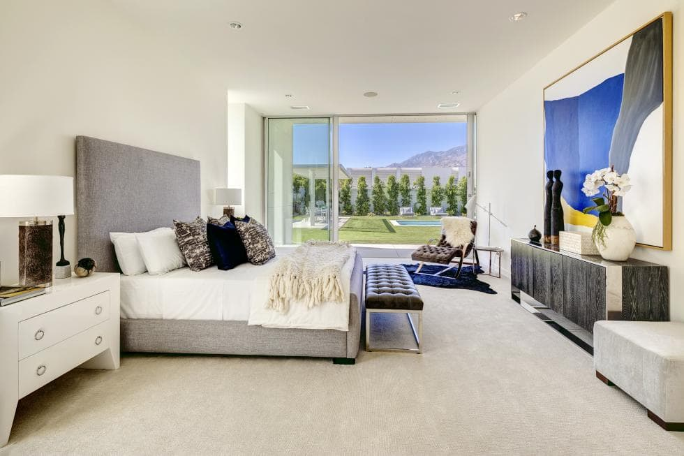 The gray frame of bed in this bedroom pairs well with the bright beige walls and ceiling. This si then complemented by bright bedside drawers and the glass wall at the far end. Image courtesy of Toptenrealestatedeals.com.