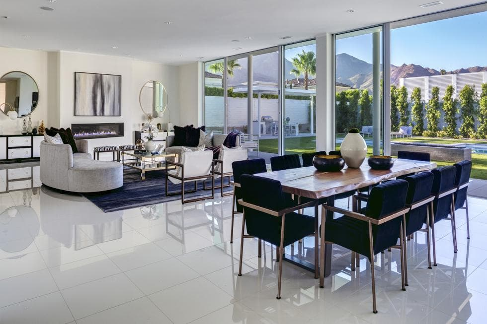 This is a look at the dining area just a few steps from the living room. This has a wooden dining table surroynded by dark chairs to contrast the white floor and the bright glass wall. Image courtesy of Toptenrealestatedeals.com.