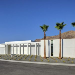 This is the front of the house with a desert landscape, tall palm trees and concrete driveway to complement the pure white exteriors of the house. Image courtesy of Toptenrealestatedeals.com.