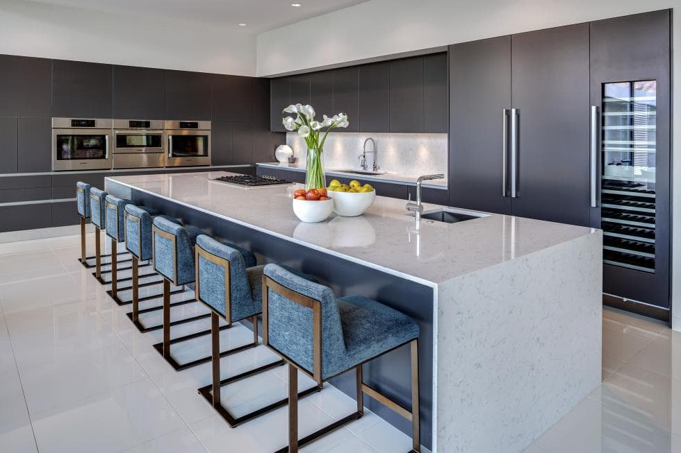 This kitchen has a large white waterfalls kitchen island that stands out against the gray modern cabinetry with stainless steel appliances. Image courtesy of Toptenrealestatedeals.com.
