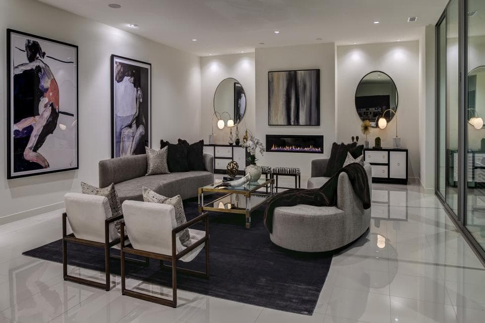 This is the living room that has pure white walls, ceiling and floor. These makes the gray sofa set stand out along with the various wall-mounted artworks and the modern fireplace. Image courtesy of Toptenrealestatedeals.com.