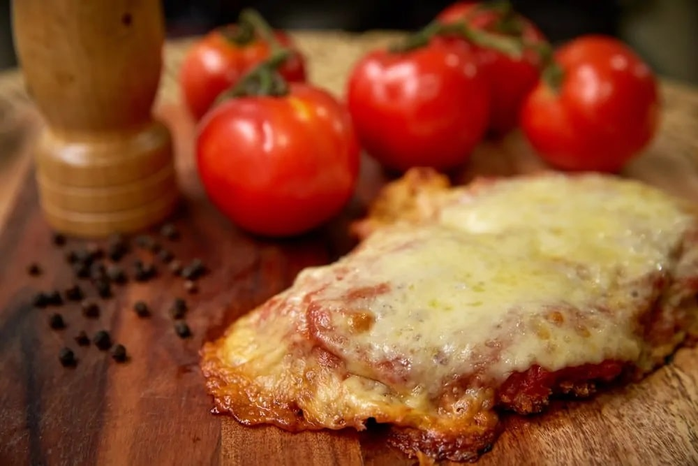 Parmigiana with fresh tomatoes on the side.