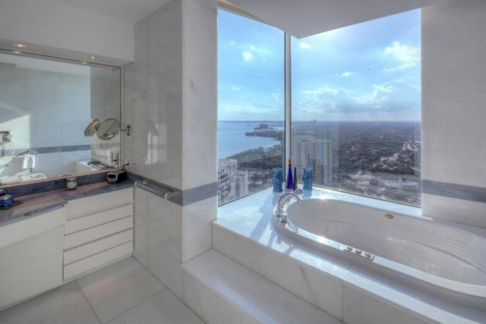 The bathroom has a bathtub embedded into the far alcove of the bathroom with glass walls for a unique look. Image courtesy of Toptenrealestatedeals.com.