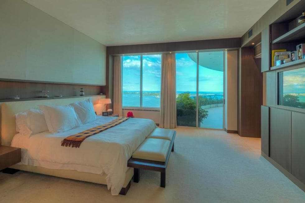 This is the spacious bedroom with a large bed and a set of glass walls on the far side to bring in natural lighting for the beige walls and ceiling. Image courtesy of Toptenrealestatedeals.com.