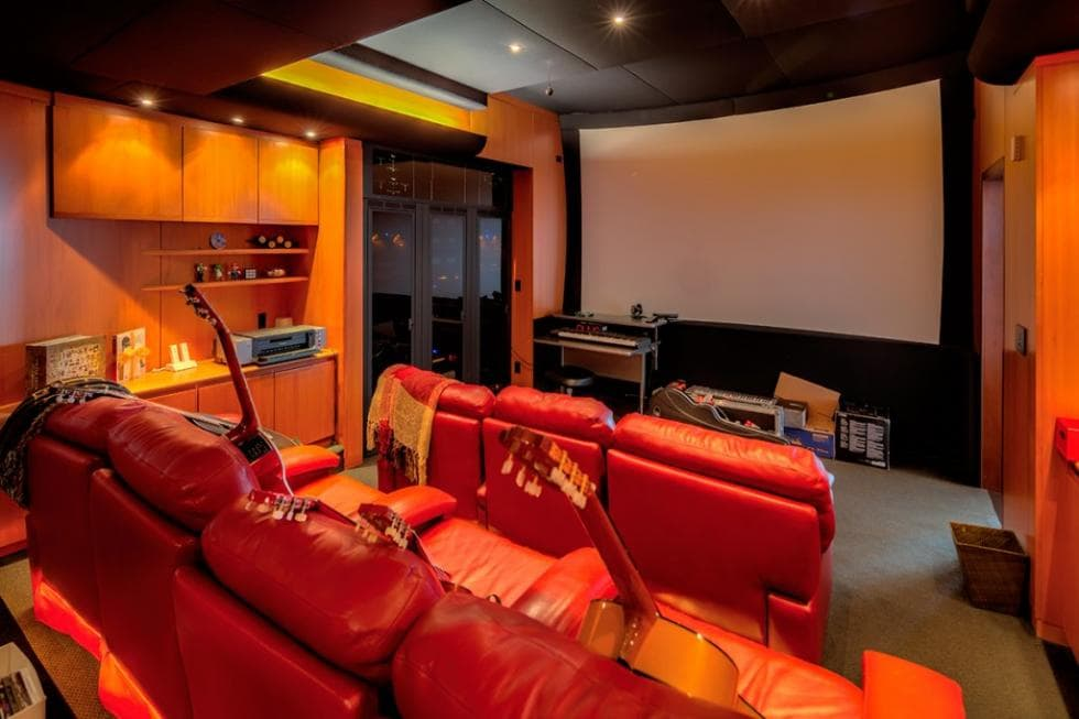This is the home theater room with bright red leather theater chairs across from the large white projector screen. Image courtesy of Toptenrealestatedeals.com.