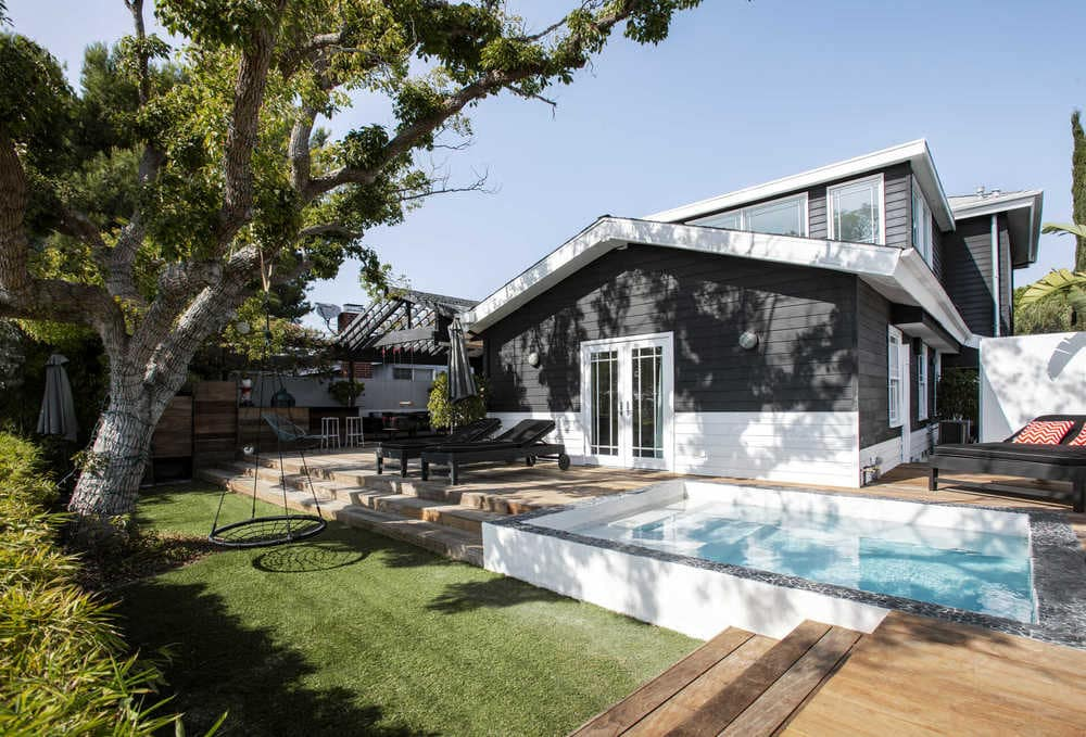 This is the back of the house as shown from the vantage of the backyard. Here you can see the grass lawn with a set of wooden stairs leading to the backyard pool that stands out against the black and white exterior wall. Image courtesy of Toptenrealestatedeals.com.