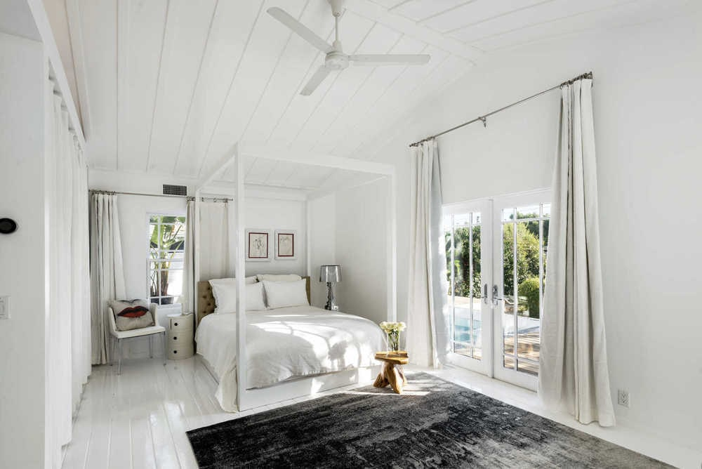 This is the primary bedroom with a large white four-poster bed and white sheets that pair well with the white walls and white wooden cathedral ceiling. Image courtesy of Toptenrealestatedeals.com.