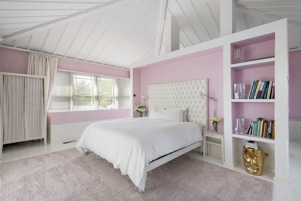 This bedroom has a white tufted bed with a large cushioned headboard. This pairs well with the white built-in wooden shelves on either side of the bed. These are then complemented by the bright pink walls. Image courtesy of Toptenrealestatedeals.com.