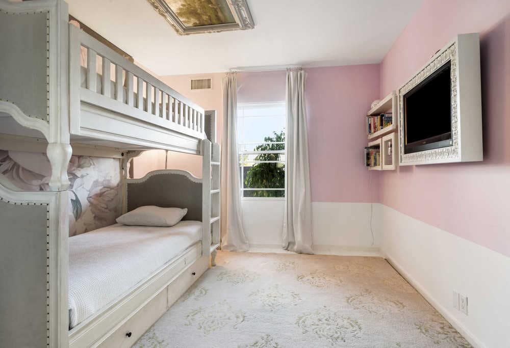 This is the kid's bedroom that has a large wooden bunk bed complemented by the pastel pink tone of the walls as well as the natural light coming from the window. Image courtesy of Toptenrealestatedeals.com.
