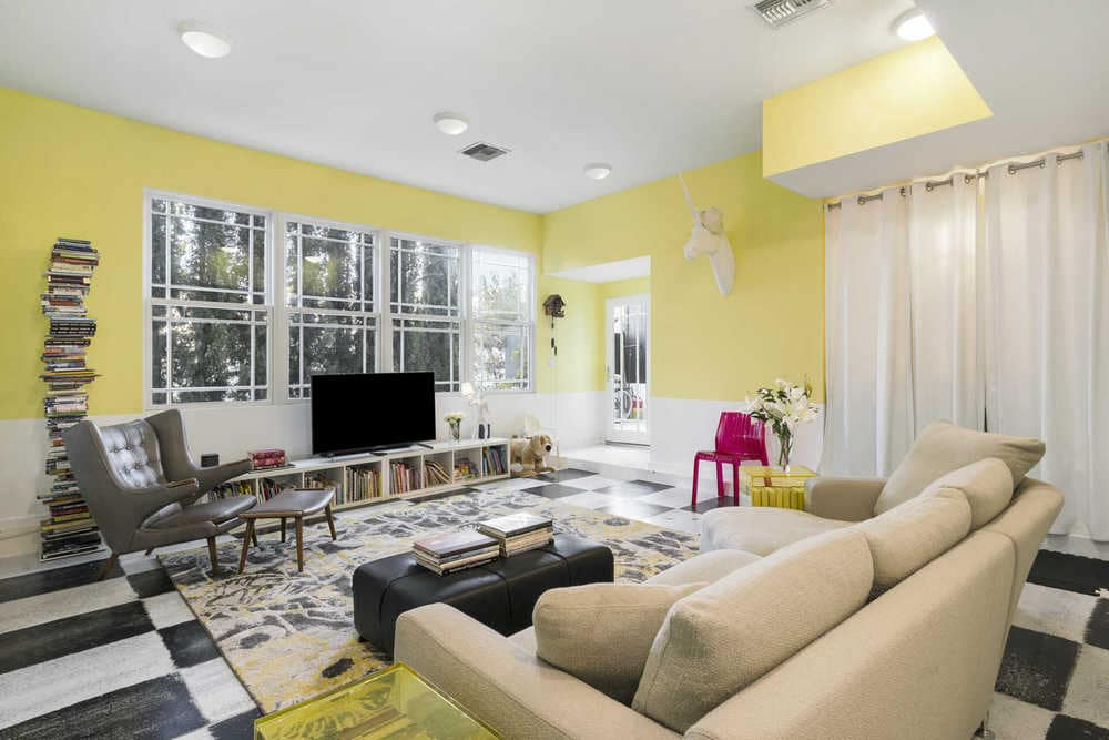 The family room has a sunny yellow pastel hue to its walls that pair well with the white wainscoting, window curtains and ceiling. Image courtesy of Toptenrealestatedeals.com.