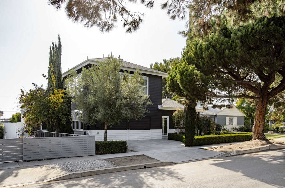 This is the front view of a house with black exterior walls accented by white and the landscaping that has tree, shrub hedges and a concrete driveway. Image courtesy of Toptenrealestatedeals.com.
