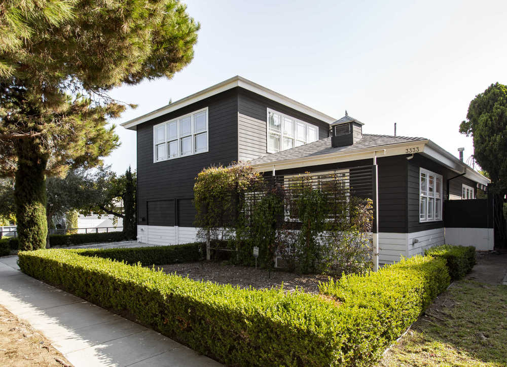 This is another look at the house that has dark exterior walls contrasted by the large windows and white accents. Image courtesy of Toptenrealestatedeals.com.