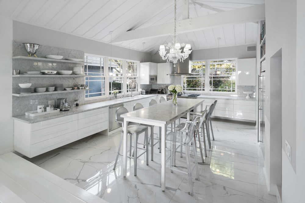 This other view of the kitchen showcases the white decorative chandelier hanging over the tall white table that matches well with the white cabinetry. Image courtesy of Toptenrealestatedeals.com.