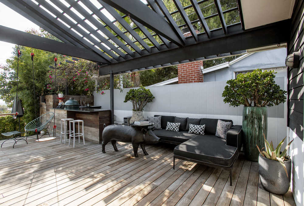 This is a look at the sitting area of the covered patio with a large L-shaped dark sofa paired with a decorative coffee table in the shape of a pig. These are then topped with a cathedral ceiling that has skylights. Image courtesy of Toptenrealestatedeals.com.