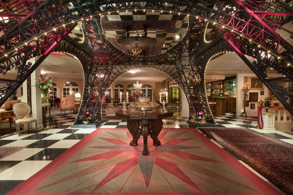 Upon entry of the house, you are welcomed by this unique and decorative foyer with a replica of the Eiffel Tower's base serving as arched entryways. Image courtesy of Toptenrealestatedeals.com.