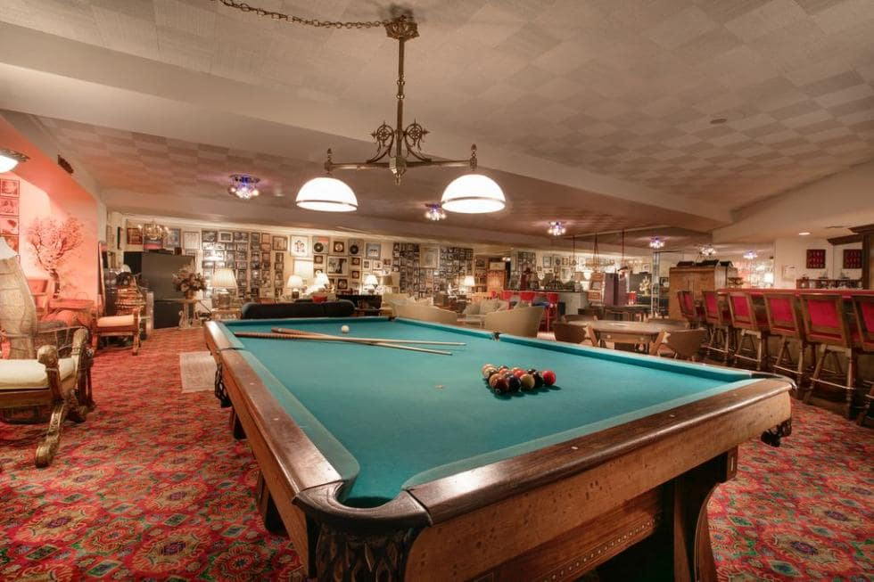 A few steps from the bar is this game area with a large pool table topped with a vintage pair of lighting. Image courtesy of Toptenrealestatedeals.com.