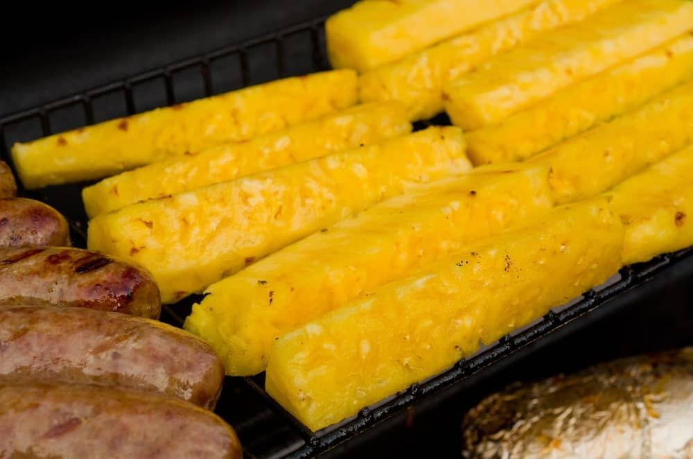 Speared pineapples on a grill.