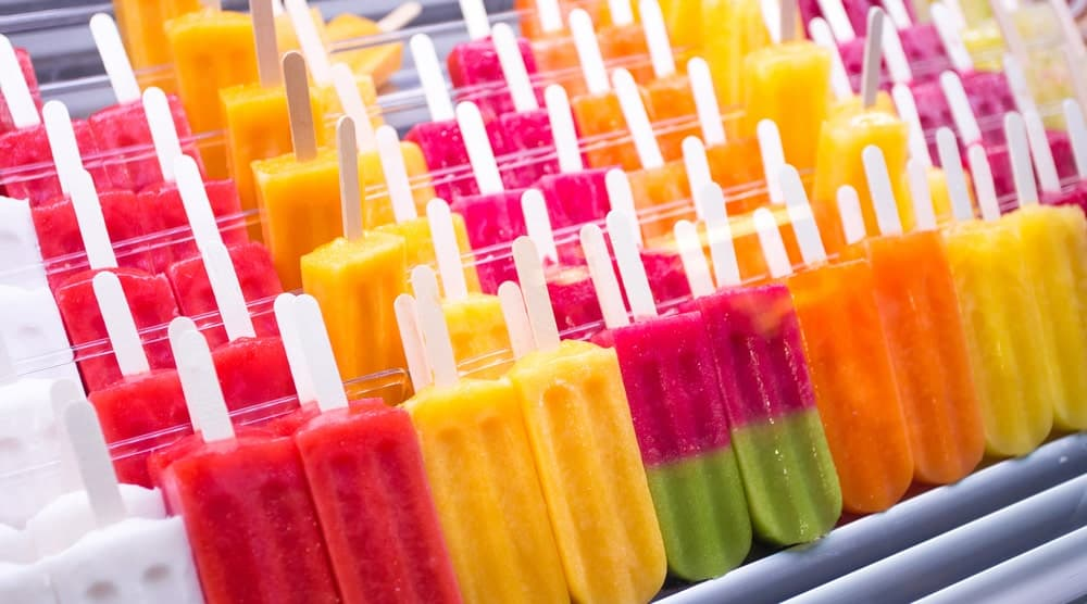Colorful popsicles on display at a market stall.