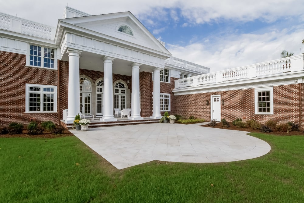 This is a look at the back of the house with a concrete courtyard before transitioning to grass lawns. You can also see here the red brick exterior walls and white pillars. Image courtesy of Toptenrealestatedeals.com.