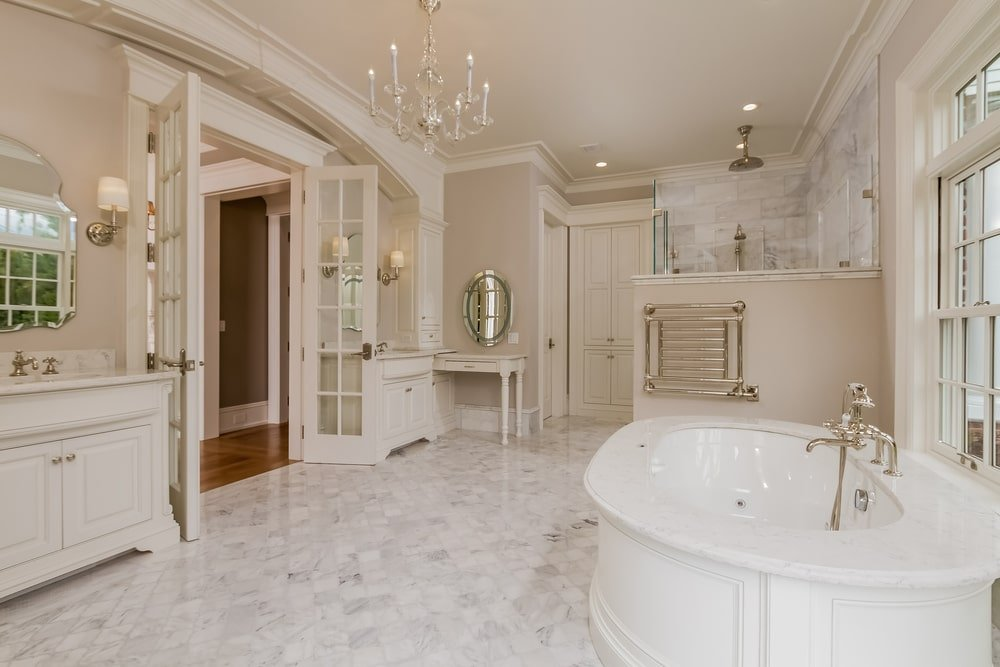This bathroom has a couple of vanities flanking the French door across from the large bathtub that blends well with the flooring tiles. Image courtesy of Toptenrealestatedeals.com.