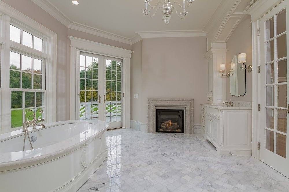 This other angle of the bathroom shows the fireplace on the far side by the vanity and the French glass doors. Image courtesy of Toptenrealestatedeals.com.
