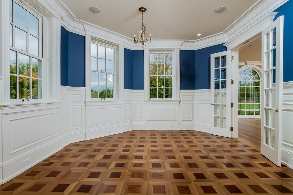 This is the formal dining room with blue walls to contrast the white wainscoting and moldings. These are then complemented by the patterned hardwood flooring. Image courtesy of Toptenrealestatedeals.com.