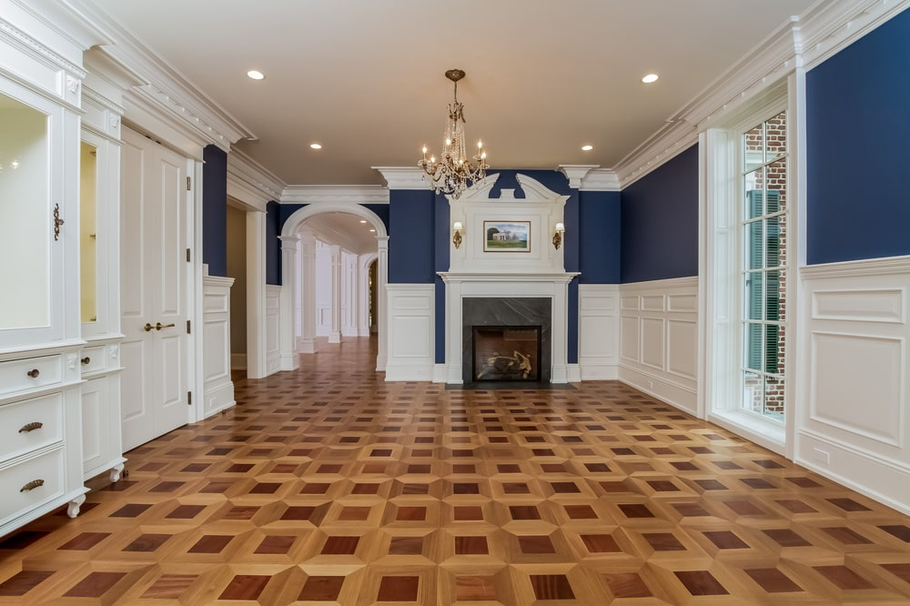 This other look at the dining room showcases the large fireplace on the far side. It has a white mantle that blends with the white wainscoting. Image courtesy of Toptenrealestatedeals.com.