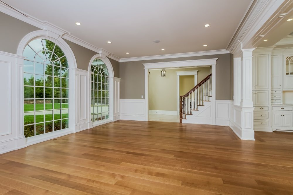 The gray walls of this room is adorned with white wainscoting that blends with the white frames of the tall arched windows. Image courtesy of Toptenrealestatedeals.com.