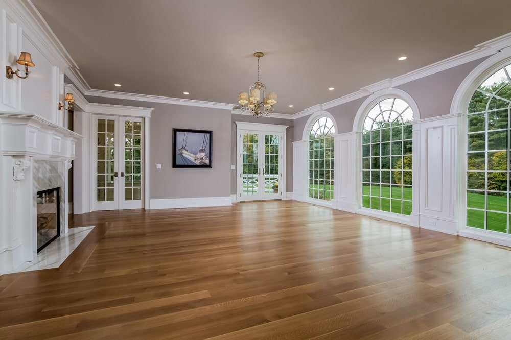This is a spacious room with tall arched windows on one side and a couple of French doors on the far side. This also has a fireplace with a mantle across from the windows. Image courtesy of Toptenrealestatedeals.com.