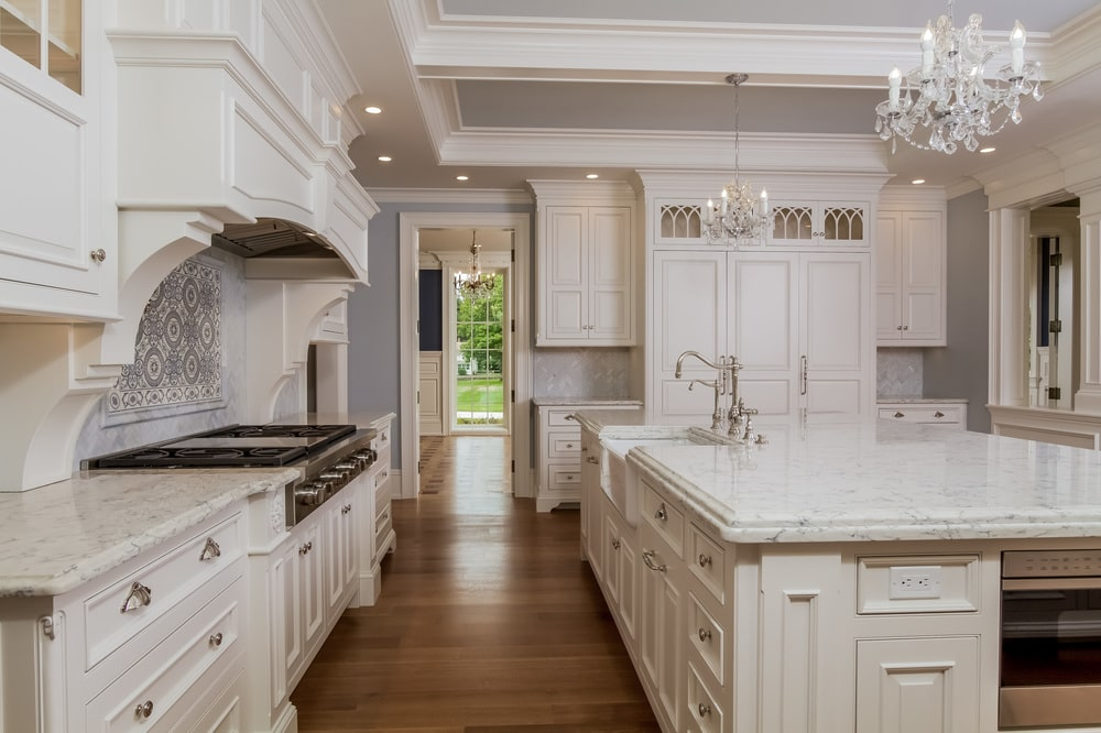 This other look at the kitchen showcases the bright beige cabinetry that matches well with the vent hood and the coffers of the ceiling. Image courtesy of Toptenrealestatedeals.com.