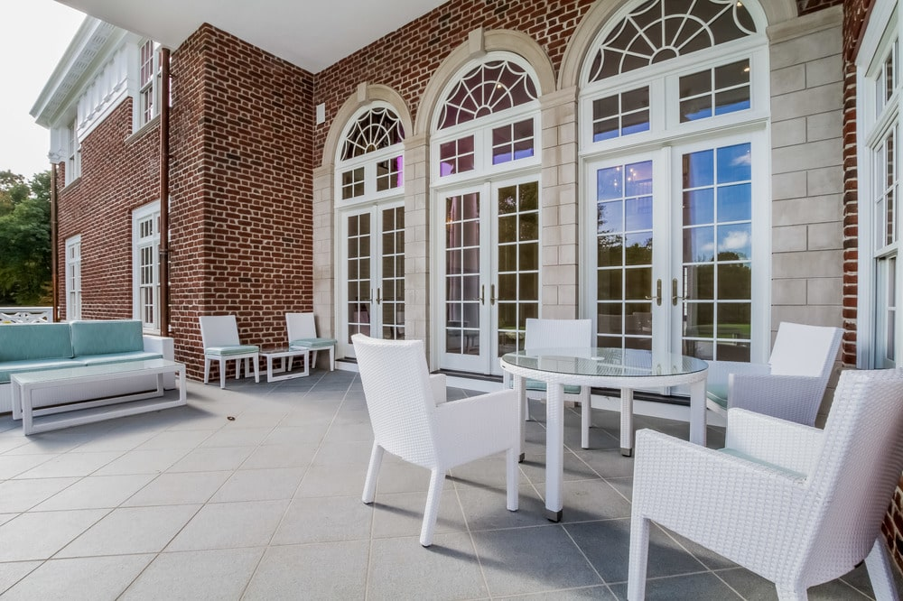 This is the back patio just outside the tall glass French doors of the living room. This area is fitted with an outdoor dining area with a round glass-top dining table. Image courtesy of Toptenrealestatedeals.com.