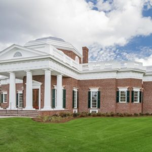 This is a look at the front of the house with red brick exterior wall and contrasting white pillars and balustrades. These are then complemented by the grass lawn and the surrounding flowering shrubs. Image courtesy of Toptenrealestatedeals.com.