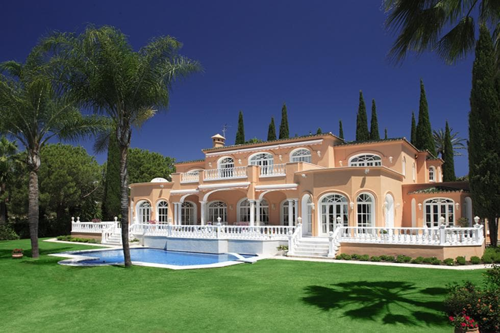 This is a look at the back of the house with bright beige exterior walls, a swimming pool surrounded by lush grass lawns and a background of tall trees. Image courtesy of Toptenrealestatedeals.com.