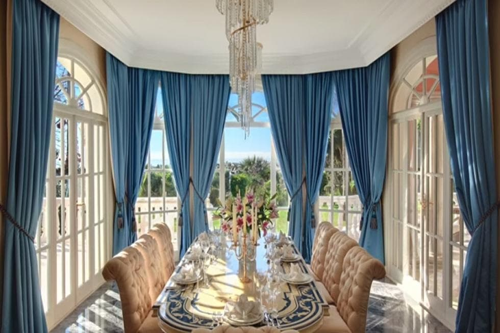 This is the formal dining room with a long dining table surrounded by tall windows with blue curtains that stand out against the natural lights and the bright ceiling. Image courtesy of Toptenrealestatedeals.com.