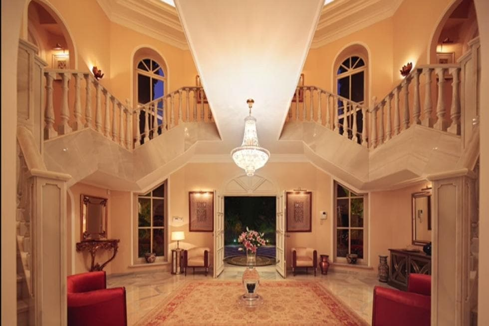 Upon entry of the house, you are welcomed by this grand foyer with a set of dual stairs, a round glass-top table in the middle of a patterned area rug and pairs of armchairs for waiting guests. Image courtesy of Toptenrealestatedeals.com.