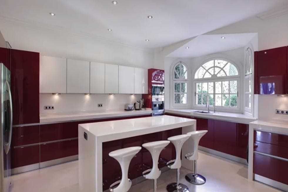 This is the bright and white kitchen with white countertops, walls and ceiling contrasted by the dark brown cabinetry. Image courtesy of Toptenrealestatedeals.com.