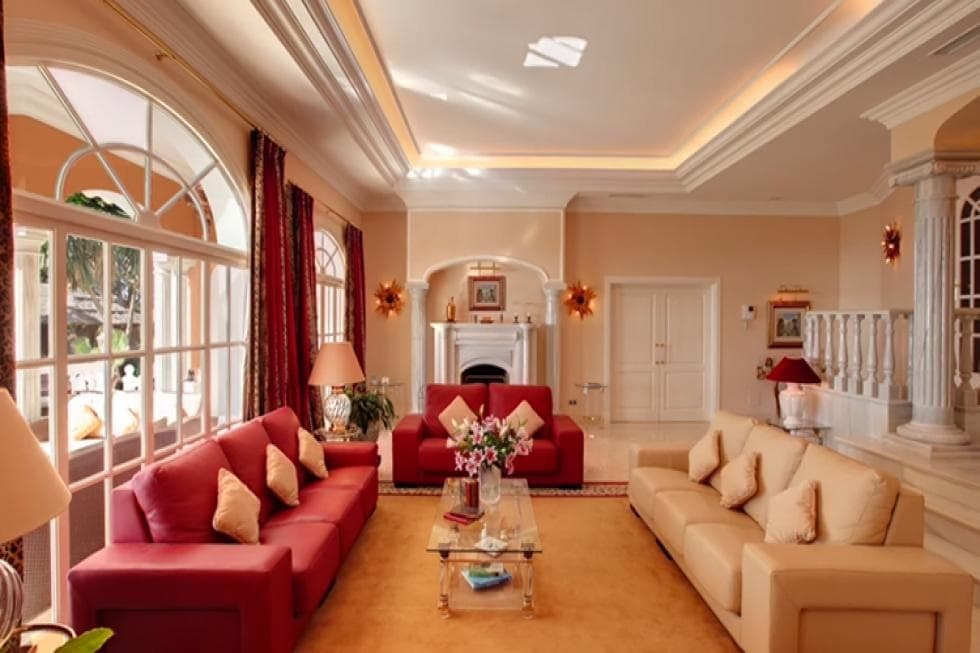 This is the formal living room with a set of red sofas to match the red curtains and a beige sofa to match the beige ceiling, walls and floor. These are surrounding a glass-top coffee table. Image courtesy of Toptenrealestatedeals.com.