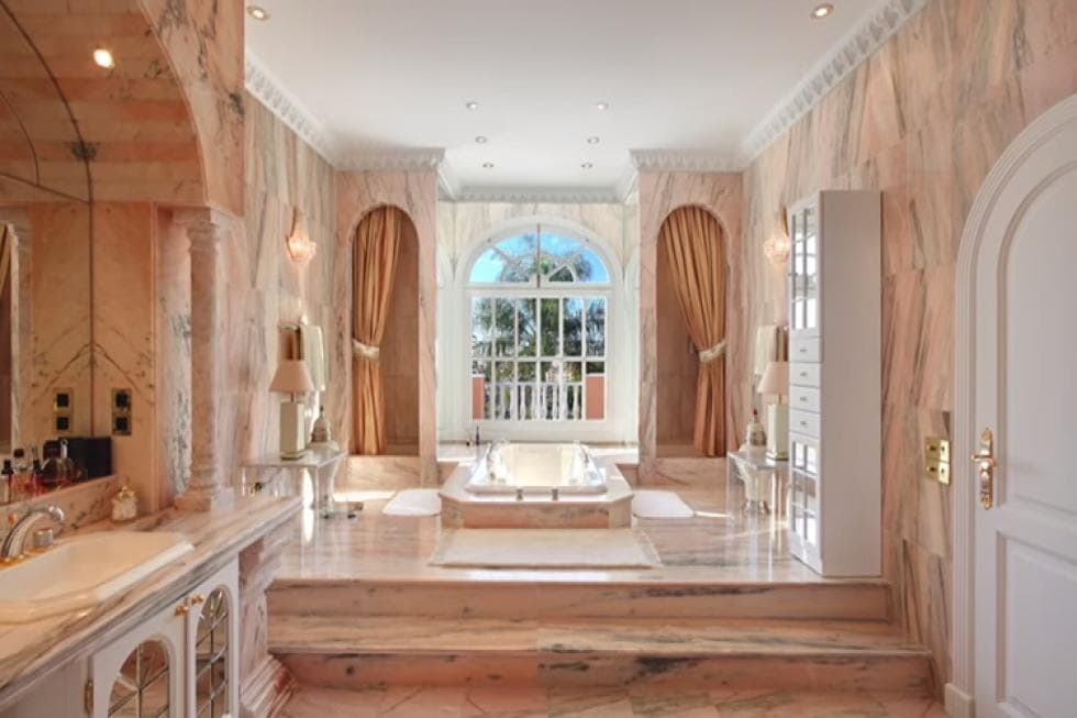 This is the spacious and airy primary bathroom with beige marble on its floors and walls to match the beige bathtub embedded into the ground on the far side surrounded by tall arched windows. Image courtesy of Toptenrealestatedeals.com.