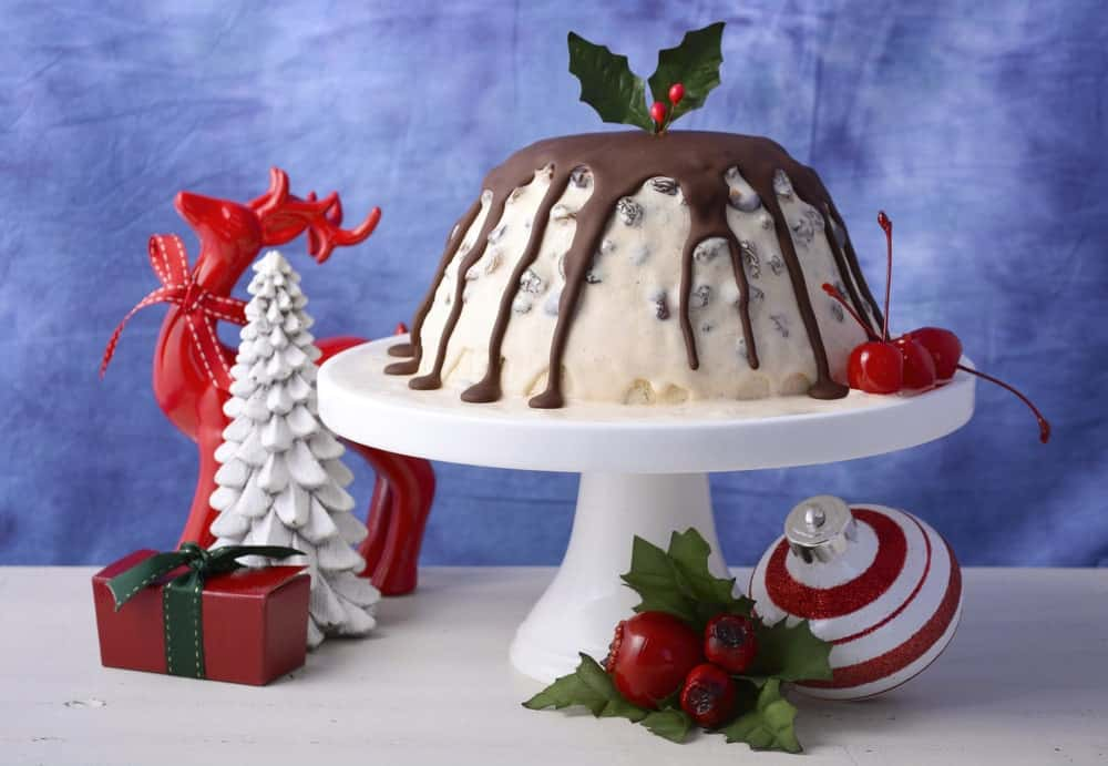 Pudding ice cream on a cake stand surrounded by Christmas decorations.