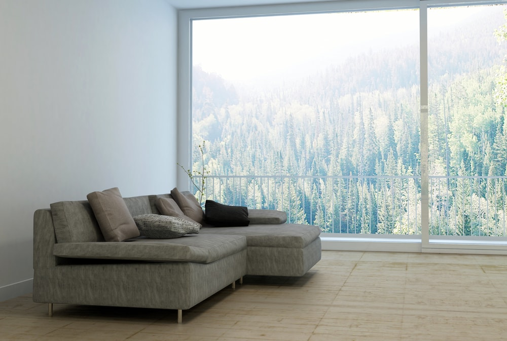 This is a side view of a light gray sectional sofa by the large window.