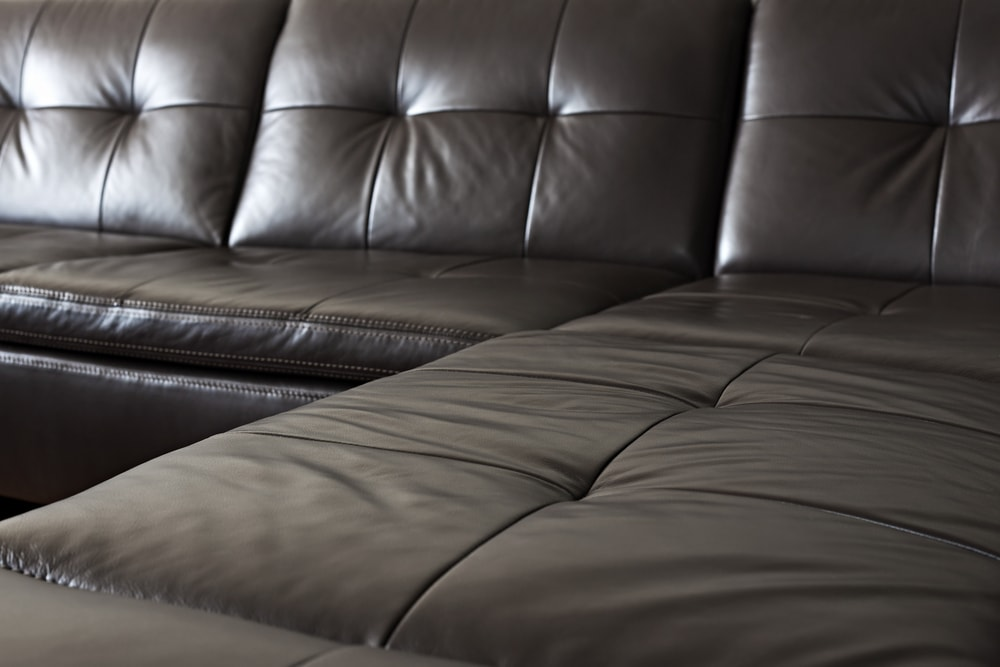 This is a close look at the black leather sectional sofa.