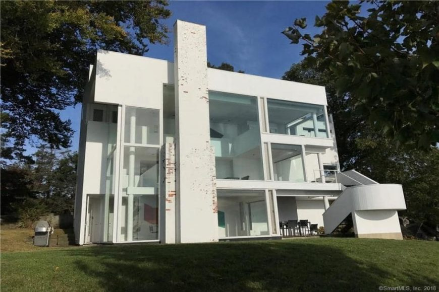 This is a look at the back of the house with white exterior walls, glass walls and a tall chimney structure that is accented with a few exposed pieces of red bricks. Image courtesy of Toptenrealestatedeals.com.