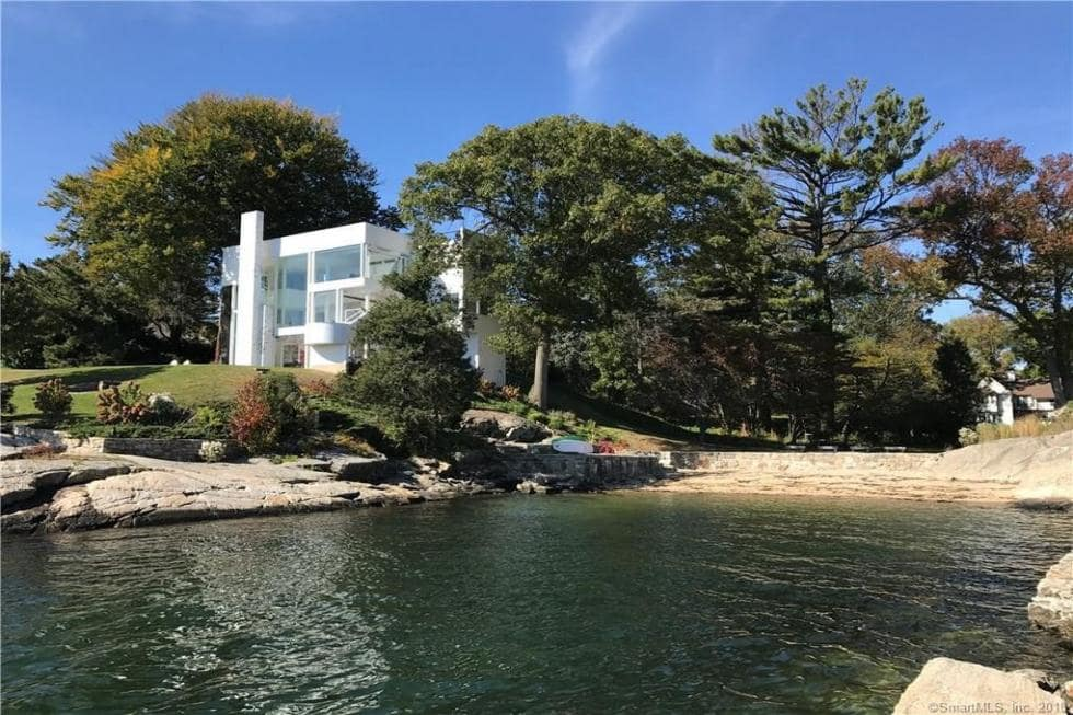 This is a look at the back of the house from the vantage of the beach. You can see here the house standing out with its white exteriors against the green landscape. Image courtesy of Toptenrealestatedeals.com.