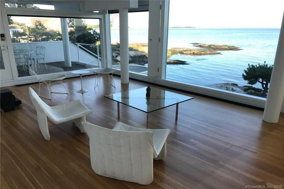 This is the living room on the first floor with a simple setup of two comfortable chairs and a glass-top coffee table to highlight the landscape outside the glass walls. Image courtesy of Toptenrealestatedeals.com.
