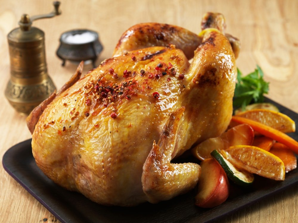 A whole grilled chicken with sides of vegetables.