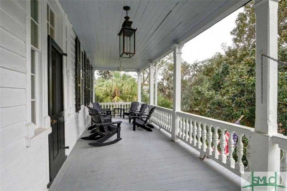 This is the balcony of the second floor with white railings, pillars and exterior walls that contrast the black elements of the lighting, chairs, doors, and shutters. Image courtesy of Toptenrealestatedeals.com.