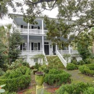 This is the front of the house with a garden of shrubs and tall trees that complement the bright white exteriors of the house. Image courtesy of Toptenrealestatedeals.com.